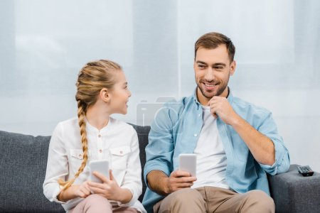 Photo for Smiling father and daughter sitting on sofa, holding smartphones and looking at each other in living room - Royalty Free Image