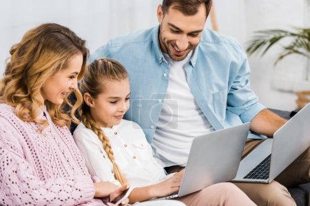 Photo for Smiling parents sitting on sofa and looking at laptop holding by cute girl - Royalty Free Image