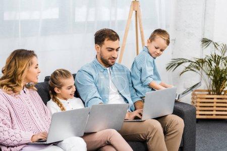 Foto de Feliz familia sentado en el sofá y usando computadoras portátiles en la sala de estar - Imagen libre de derechos