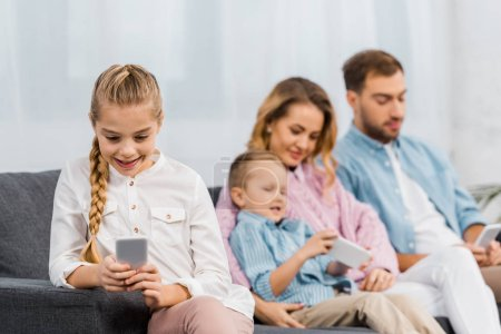 Photo for Cute girl sitting on sofa and using smartphone  with family at background in living room - Royalty Free Image