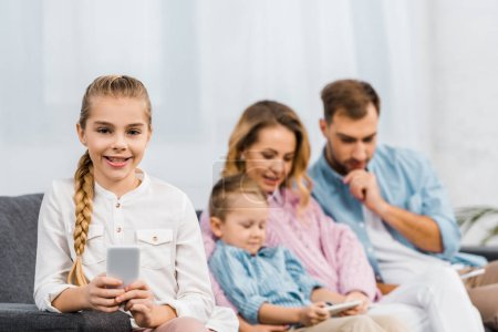 Photo for Smiling girl sitting on sofa, holding smartphone and looking at camera with family at background in apartment - Royalty Free Image