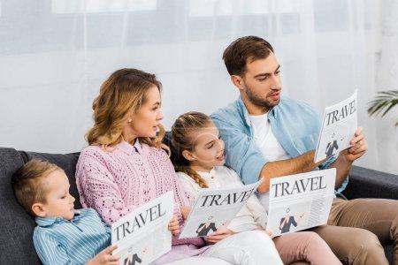 Foto de Feliz familia sentado en el sofá y leer diarios de viaje de apartamento - Imagen libre de derechos