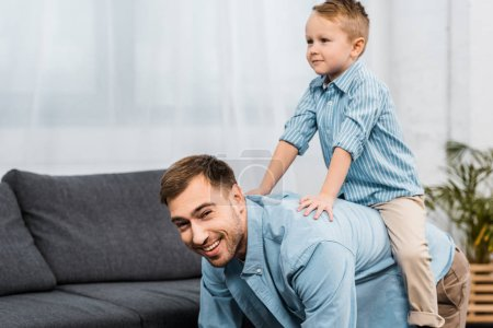 Photo for Father standing on all fours and looking at camera while cute boy sitting on back in apartment - Royalty Free Image