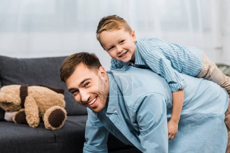 Photo for Cheerful boy sitting on back of father standing on all fours and looking at camera in apartment - Royalty Free Image