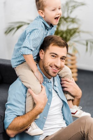 Photo for Smiling boy sitting on shoulders of father looking at camera in living room - Royalty Free Image