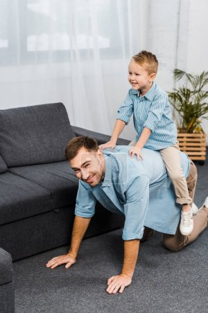 Photo for Smiling boy sitting on back of father standing on all fours and looking at camera in living room - Royalty Free Image