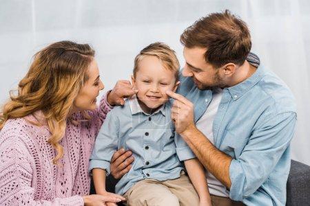 Foto de Padres felizes sentado en sofá y tocar con las mejillas de los dedos del hijo sonriente en Apartamento - Imagen libre de derechos