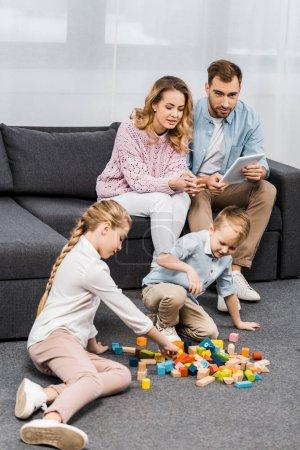 Photo pour Parents, assis sur le canapé avec tablette numérique et en regardant les enfants jouer avec des blocs de bois multicolores étage en appartement - image libre de droit