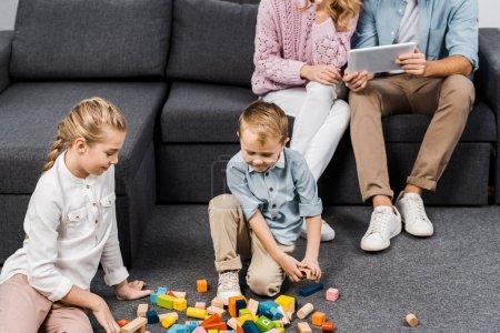 Photo pour Vue recadrée de parents assis sur le canapé et à l'aide d'une tablette numérique tandis que les enfants jouer avec des blocs de bois multicolores sur le plancher dans le salon - image libre de droit