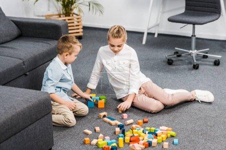 Foto de Lindo niño y una niña sentada en el piso y jugando con bloques de madera multicoloras en sala de estar - Imagen libre de derechos