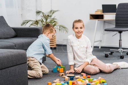 Photo pour Jolie fille assis sur le sol et en regardant la caméra tout garçon jouant avec multicolores en bois bloque dans appartement - image libre de droit