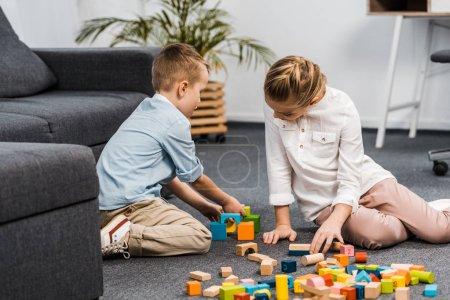 Foto de Linda chica y el muchacho sentado en el piso y jugando con multicolor madera bloques de apartamento - Imagen libre de derechos