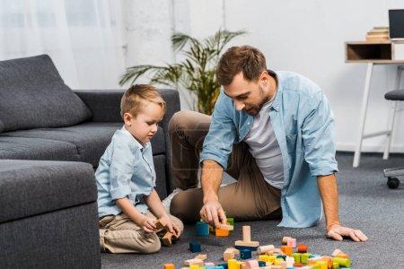 Foto de Hombre guapo y lindo niño jugando con bloques de madera multicoloras piso apartamento - Imagen libre de derechos