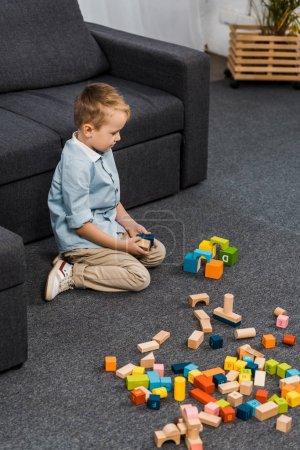 Foto de Niño lindo con bloques de madera multicoloras sentado en piso de living comedor - Imagen libre de derechos