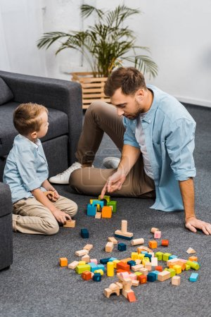 Photo for Handsome father and cute son playing with multicolored wooden blocks on floor in living room - Royalty Free Image