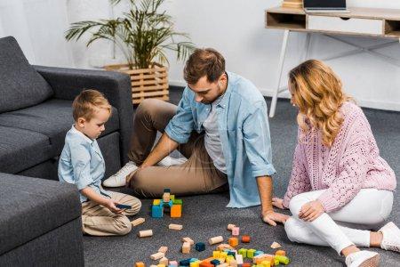 Foto de Madre, padre e hijo lindo jugando con bloques de madera multicoloras de piso en sala de estar - Imagen libre de derechos