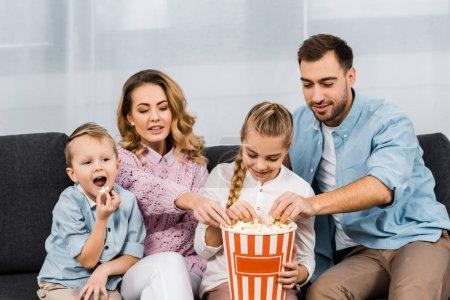 Photo pour Heureuse famille assis sur le canapé, regarder la tv et manger des pop corn de seau rayé dans le salon - image libre de droit