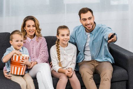 Photo for Handsome father sitting on sofa and changing channels by remote controller with smiling  wife and daughter and son eating popcorn in apartment - Royalty Free Image