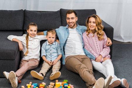 Foto de Sonrisa de padre, madre, hija e hijo trastornado sentado en piso cerca de sofá en el apartamento - Imagen libre de derechos