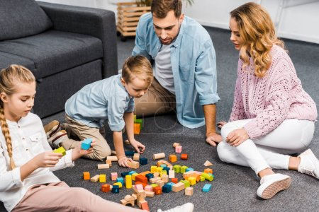 Photo for Parents and siblings playing with wooden blocks on floor in living room - Royalty Free Image