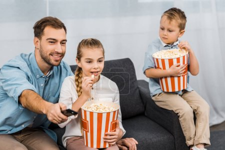 Photo for Smiling father sitting on sofa and changing channels by remote controller with children holding striped buckets and eating popcorn in apartment - Royalty Free Image