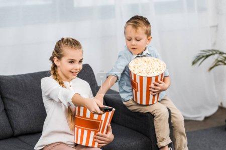 Photo pour Jeune fille souriante assise sur le canapé et changer de chaîne avec la télécommande avec frère manger maïs éclaté en appartement - image libre de droit