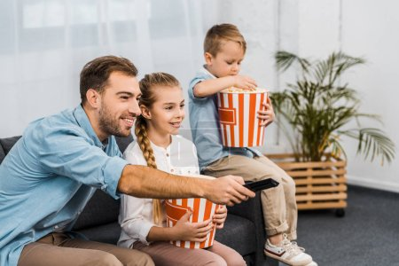Photo for Smiling father sitting on sofa and changing channels by remote controller with children holding striped popcorn buckets in apartment - Royalty Free Image