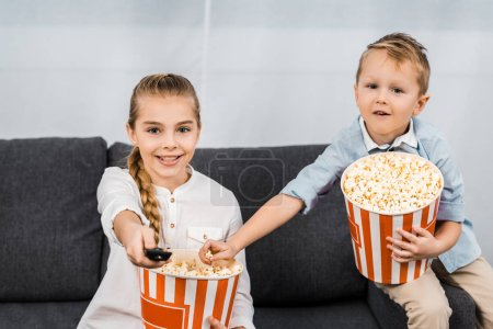 Photo for Smiling siblings sitting on sofa, holding striped popcorn buckets and changing channels by remote controller - Royalty Free Image