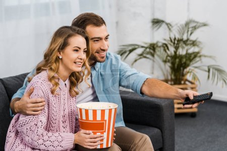 Photo for Smiling man sitting on sofa, holding remote controller and embracing wife with striped popcorn bucket - Royalty Free Image