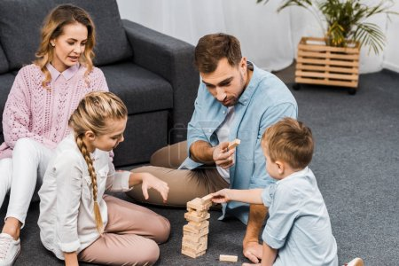 Photo for Two parents playing blocks wood tower game with children on floor in apartment - Royalty Free Image