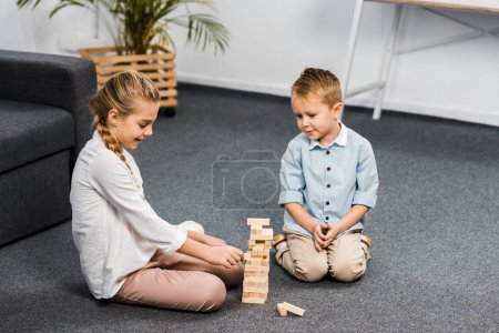 cute siblings sitting on floor and playing blocks wood tower game in living room