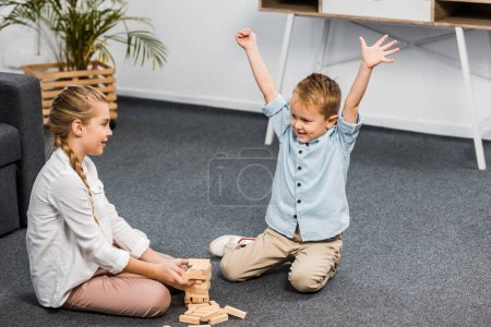 Photo for Happy boy with raising hands and cute girl sitting on floor and playing blocks wood tower game in apartment - Royalty Free Image