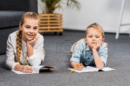 Photo pour Jolie fille et garçon couché sur le plancher, écriture dans les carnets et regardant la caméra dans le salon - image libre de droit