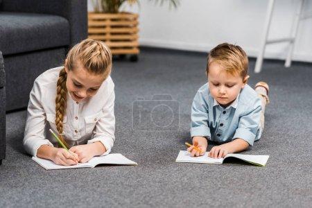 Photo pour Jolie fille et garçon couché sur le sol et l'écriture dans les ordinateurs portables dans la salle de séjour - image libre de droit