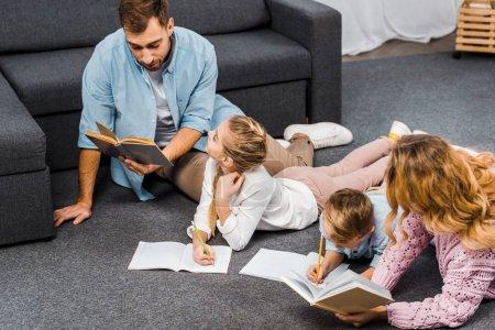 Photo pour Parents qui lisent des livres tandis que les enfants écrivant dans les carnets de chaussée en appartement - image libre de droit