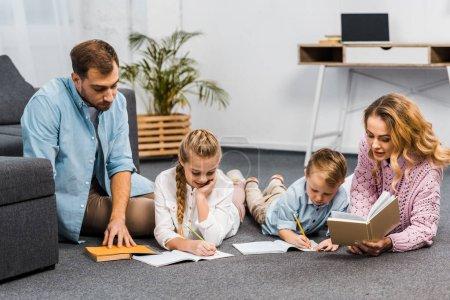Photo pour Parents qui lisent des livres tout en frères et sœurs par écrit dans les cahiers d'exercices étage en appartement - image libre de droit