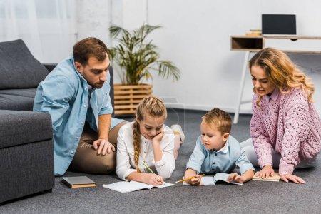 Photo pour Parents en regardant fille et garçon couché sur le sol et l'écriture dans les cahiers d'exercices en appartement - image libre de droit