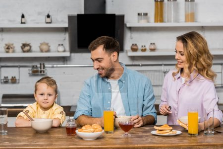 Photo for Smiling parents looking at cute boy sitting at kitchen table - Royalty Free Image