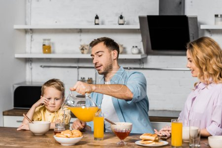 Photo for Pretty woman and cute boy looking at handsome man pouring orange juice in glass in kitchen - Royalty Free Image