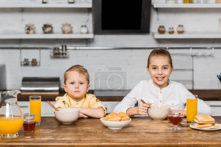 Photo for Pretty siblings looking at camera and sitting at table with cookies, toasts and bowls with porridge - Royalty Free Image