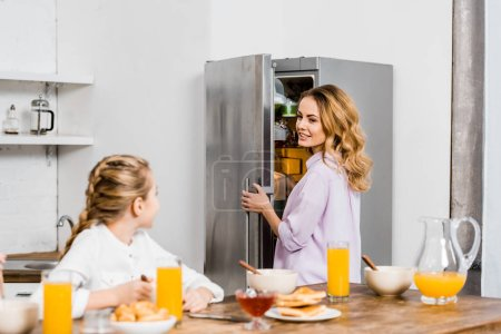 Photo for Girl sitting at table and looking at mother opening fridge - Royalty Free Image