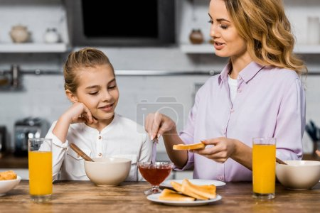 Photo for Smiling girl looking at pretty woman spreading jam on toast in kitchen - Royalty Free Image