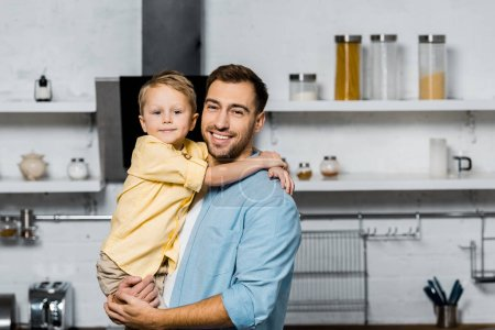 Photo for Handsome father and cute son hugging and looking at camera in kitchen - Royalty Free Image
