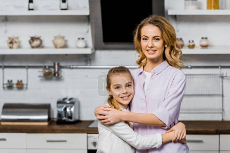 Photo for Attractive woman and cute daughter hugging and looking at camera in kitchen - Royalty Free Image