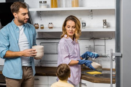 Photo for Handsome man holding bowls and looking at pretty wife washing dishes and talking with son - Royalty Free Image