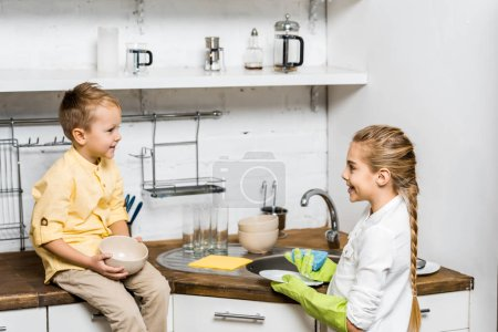 Photo for Cute girl in rubber gloves washing dishes and looking at smiling boy sitting on table and holding bowl in kitchen - Royalty Free Image