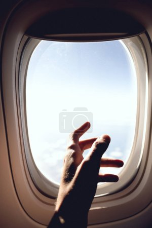 partial view of man in airplane and blue cloudy sky