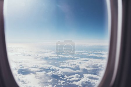 view of blue cloudy sky from airplane window