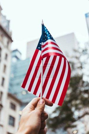 Photo pour Recadrée tir d'homme tenant le drapeau américain dans la main avec floue rue new york city sur fond - image libre de droit