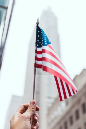 Photo for Cropped shot of man holding american flag in hand with blurred new york city street on background - Royalty Free Image